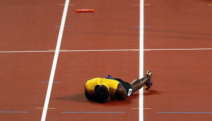Usain Bolt leżący na bieżni Stadionu Olimpijskiego w Londynie